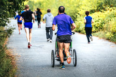 Male runner running marathon. In autumn city Park with a pram baby Royalty Free Stock Photo