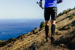 Male runner running mountain trail. With hiking sticks  in background sea Royalty Free Stock Photos