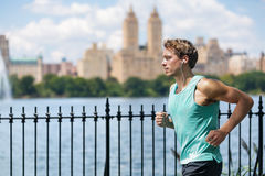 Male runner running in New York City Central Park. During summer travel along the lake with view on skyscrapers background. New yorker living a healthy and fit Royalty Free Stock Photography