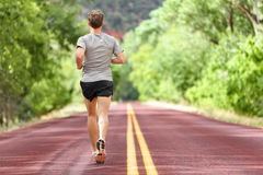 Male runner running on road training for fitness. Man doing jogging workout run outside in summer in nature. Athlete in running shoes and shorts working out Royalty Free Stock Image