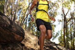 Male runner running on rocky mountain trail. Fit young man in sportswear running down the hill over rocky path royalty free stock photo