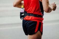 Male runner running. Street on back of bottle water Royalty Free Stock Image