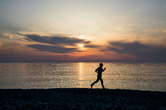 Male runner silhouette on the beach. At sunset Royalty Free Stock Images