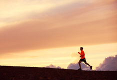 Male runner silhouette, running into sunset. Male runner silhouette, Man running into sunset, colorful sunset sky Stock Photo