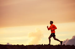 Male runner silhouette, running into sunset Stock Photography