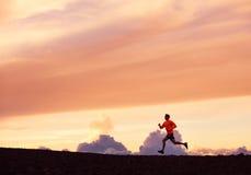 Male runner silhouette, running into sunset. Male runner silhouette, Man running into sunset, colorful sunset sky Stock Images