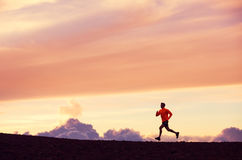 Male runner silhouette, running into sunset. Male runner silhouette, Man running into sunset, colorful sunset sky Royalty Free Stock Image
