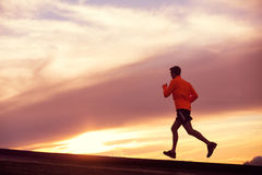 Male runner silhouette, running into sunset. Male runner silhouette, Man running into sunset, colorful sunset sky Royalty Free Stock Images