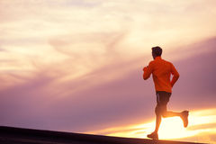 Male runner silhouette, running into sunset. Male runner silhouette, Man running into sunset, colorful sunset sky Stock Photography