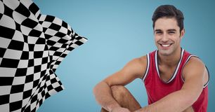 Male runner sitting on track against blue background with checkered flag Stock Photography