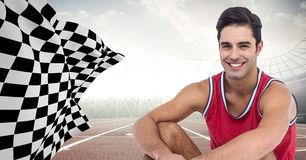 Male runner sitting on track against flares with checkered flag. Digital composite of Male runner sitting on track against flares with checkered flag Stock Image