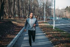Male runner in sportswear on training outdoor. Jogger on morning workout. Athletic man running marathon Stock Image