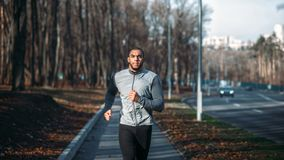 Male runner in sportswear on training outdoor. Jogger on morning workout. Athletic man running marathon Royalty Free Stock Images