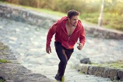 Male runner sprinting outdoor. Full length shot of healthy young man running along the climb, male runner sprinting outdoor Stock Photos