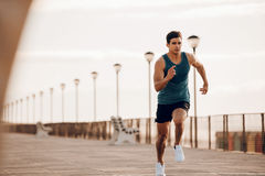 Male runner sprinting outdoors in morning. Full length shot of healthy young man running on the promenade. Male runner sprinting outdoors Royalty Free Stock Photography