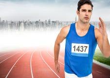 Male runner sprinting on track against blurry skyline. Digital composite of Male runner sprinting on track against blurry skyline Royalty Free Stock Photo