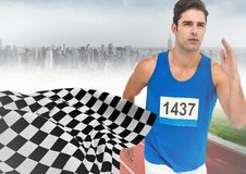 Male runner sprinting on track against misty skyline and checkered flag Stock Images