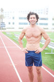 Male runner in stadium. Athetlic muscular male runner standing in a stadium Stock Image