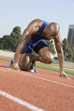 Male Runner In The Start Up Position. Full length of an African American male runner in the start up position at racetrack Royalty Free Stock Photography