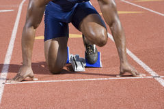 Male Runner At Starting Block. Low section of African American male athlete at starting block in race track Royalty Free Stock Image