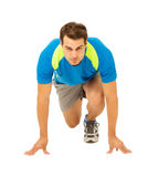 Male Runner At The Starting Block Before Race. Full length portrait of determined male runner at the starting block before race over white background. Vertical Royalty Free Stock Photo