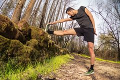 Male runner stretching outdoors. On nature in misty forest full of pleasure warm light. Standing Hamstring Stretch on old stone wall Royalty Free Stock Image