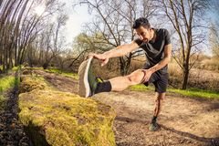 Male runner stretching outdoors. On nature in misty forest full of pleasure warm light. Standing Hamstring Stretch on old stone wall Royalty Free Stock Photography