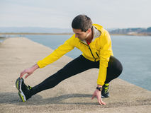 Male runner stretching. On a river dock Stock Photo