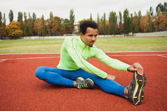 Male runner stretching before workout. African runner stretching before workout. The guy preparing for training Royalty Free Stock Photos