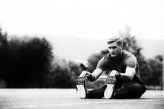 Male Runner Stretching Before Workout. Young Athlete Man Relax and Strech Ready for Run at Athletics Race Track on Stadium Royalty Free Stock Image
