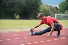 Male Runner Stretching Before Workout. Young Athlete Man Relax and Strech Ready for Run at Athletics Race Track on Stadium Stock Photos