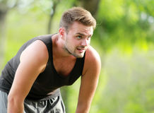 Male runner taking a break after a tired running. Portrait of male runner taking a break after a tired running with copy space Stock Images