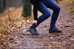 Male runner touching cramped calf at jogging. Male runner touching cramped calf at morning jogging. Achilles tendon pain or injury concept background stock photo