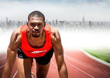 Male runner on track against blurry skyline. Digital composite of Male runner on track against blurry skyline Royalty Free Stock Images