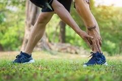 Male runner training in cold winter doing warm-up leg stretching. Exercise Stock Photos