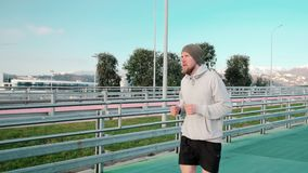 Male runner is training on stadium in open air in sunny weather. Jogger man is running on soft track for jog in open olympic stadium. He is doing work out for stock video