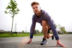 Male runner training in starting position Stock Photos