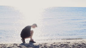 Male runner tying  his shoelaces in the sun light on the beach slow motion. Male runner tying  his shoelaces in the sun light on the beach stock video