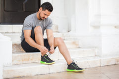 Male runner tying his shoes. Handsome young man with a beard tying his shoes before exercising outdoors in the city Stock Photo