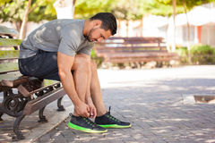 Male runner tying his shoes before training. Profile view of an attractive young man tying his shoes and getting ready to go for a run outdoors Stock Photography