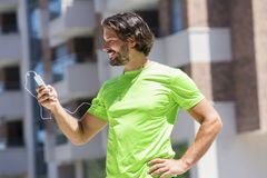 Male runner using mobile phone outdoor. Portrait of male runner using mobile phone outdoor Royalty Free Stock Photo