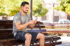 Male runner using a smartphone at the park. Handsome young male runner taking a break in a park bench and using his smartphone to update his social media status Stock Images