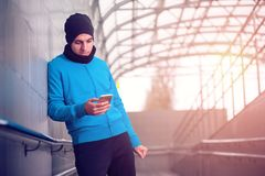Male runner using smartphone workout app. Handsome fitness man exercising outdoors in urban city location Royalty Free Stock Image
