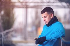 Male runner using smartphone workout app. Handsome fitness man standing in urban city location Stock Image