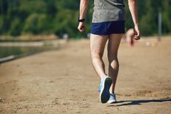 A male runner walks after training in the park . A male runner walks after training in the park in the summer Royalty Free Stock Image