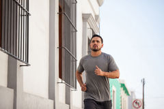 Male runner working out in the city. Good looking young male runner focused on his training and jogging around the city Royalty Free Stock Photos