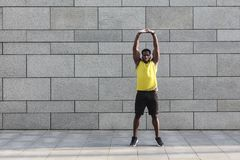 Male runner in yellow sportswear stretching before doing morning. Workout. Young African jogger warming up before outdoor run Royalty Free Stock Images
