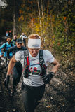 Male runners run group on a dirt road in woods Stock Photography
