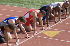 Male Runners At Starting Blocks. Group of multiethnic male runners at starting blocks in racetrack Royalty Free Stock Image
