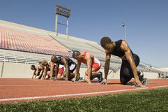 Male Runners At Starting Blocks. Group of multiethnic male runners at starting blocks in racetrack Stock Photo